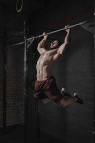 Young crossfit athlete doing pull-ups at the gym. Handsome man doing functional training. Practicing calisthenics.